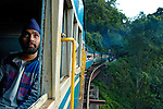 Indian man travelling in the Nilgiri Mountain Railway.  The steam train is crossing one of the many bridges between Coonoor and Metapulayam. Part of the journey is managed only by a rack-and-pinion system. India, Tamil Nadu. --- Info: The Nilgiri Mountain Railway (NMR) is the only rack railway in India and connects the town of Mettupalayam with the hill station of Udagamandalam (Ooty), in the Nilgiri Hills of southern India. The construction of the 46km long meter-gauge singletrack railway in Tamil Nadu State was first proposed in 1854, but due to the difficulty of the mountainous location, the work only started in 1891 and was completed in 1908. This railway, scaling an elevation of 326m to 2,203m and still in use today, represented the latest technology of the time. In July, UNESCO added the NMR as an extension to the World Heritage Site of Darjeeling Himalayan Railway.