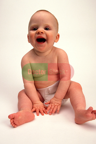 baby laughing in diaper on white background