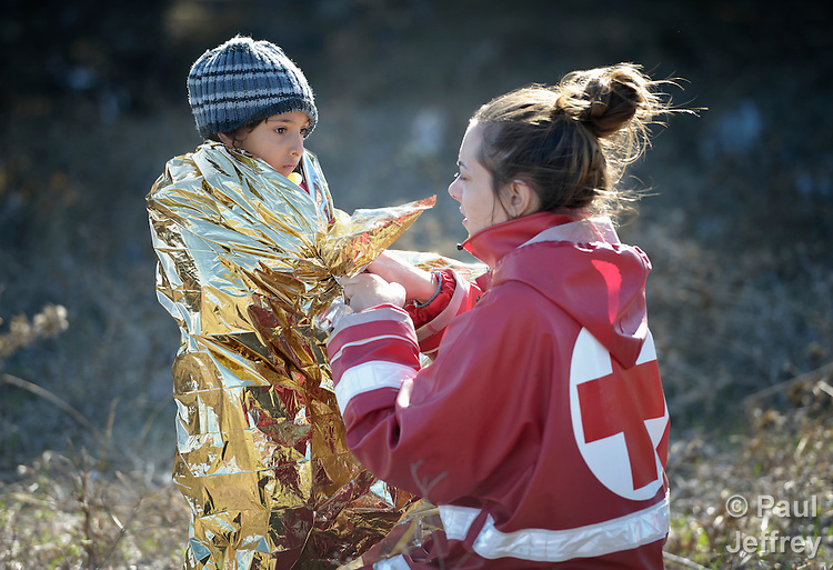 Konstantina Koulouri, a volunteer with the Greek Red Cross, wraps an insulating blanket around Hajem, a 2-year old Syrian refugee who just arrived on the Greek island of Lesbos. The boy was sopping wet from transiting the Aegean sea in a small boat with his family.