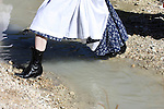 A Lady in late 1800s period western clothing with long dress jumping a small stream