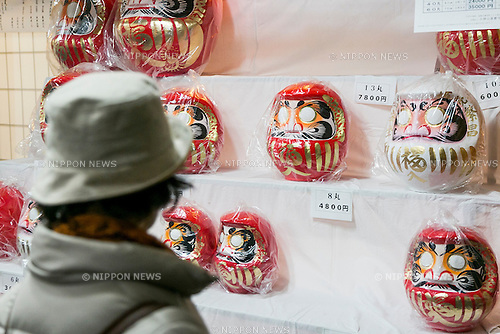A woman looks at the Daruma dolls on sale at the Shorinzan Daruma Temple in Takasaki City, Gunma Prefecture on January 6, 2016, Japan. Every year thousands of people visit the country's most famous Daruma market (Daruma ichi) held at the Shorinzan Daruma Temple on January 6 and 7. Takasaki City, is known as the capital of Daruma dolls and about 80% of Japan's Daruma are produced there. According to the tradition, Daruma dolls are sold without pupils painted on their eyes. People color in one pupil when a wish is made or a goal set, and when the wish comes true or the goal is achieved they fill in the other pupil. At the end of the year, used Daruma dolls are returned to the temple to be burned. (Photo by Rodrigo Reyes Marin/AFLO)
