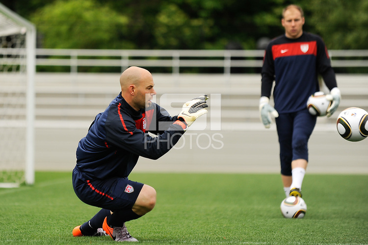Goalkeeper Marcus Hahnemann plays a ball as Brad Guzan watches during the U. S. men's national team practice at Princeton University in Princeton, NJ, on May 19, 2010.