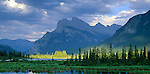 Banff National Park, Canada    Mount Rundle and Sulphur Mountain reflecting on Vermillion Lakes with sun breaks lighting the distant wetland trees
