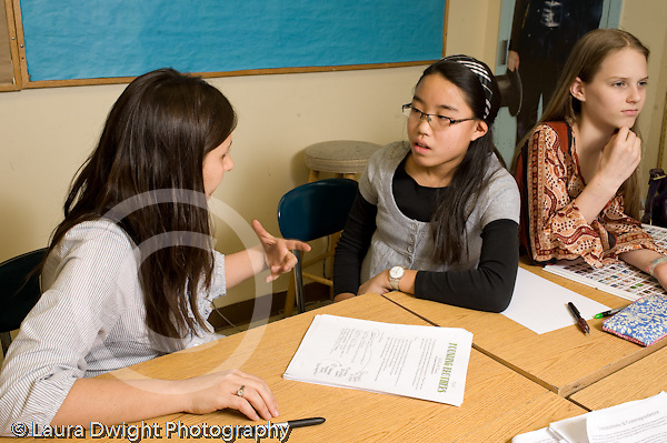 Public Middle School Grade 7 humanities English History female teacher talking with female student about project horizontal