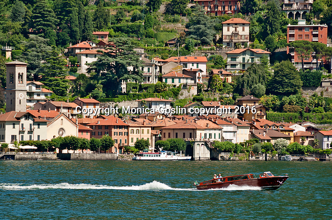 A boat passes in front of Torno, a town on Lake Como just north of Como, Italy