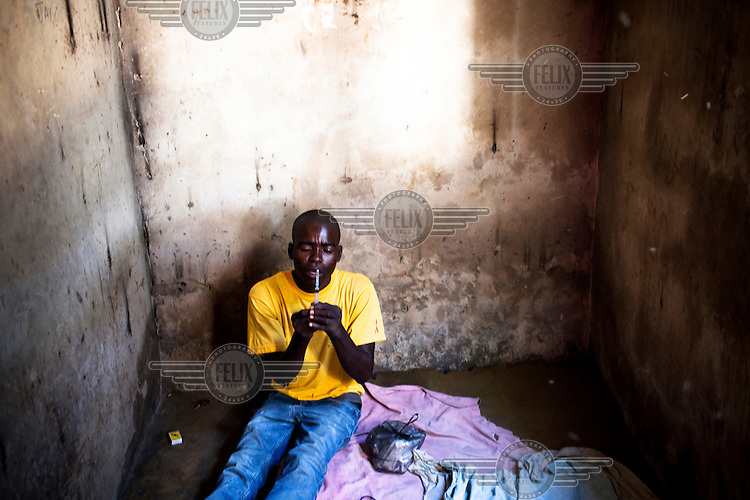 A drug user prepares to take heroin in Dar Es Salaam.