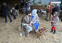 NWA Media/Michael Woods --12/21/2014-- w @NWAMICHAELW...Zach and Kelsey Ayres play the role of Mary and Joseph as they talk with Jillian Grau , age 4, and other visitors at the living nativity at the Bella Vista Christian Church Sunday evening in Bella Vista.  It is the second year for the church to offer the live nativity to the community, with a new feature of  live camels for this years display.