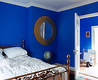 The ultramarine blue walls of the bedroom of this apartment create a bright and fresh feel in conjunction with white cotton bedding and an en-suite bathroom has been painted to match