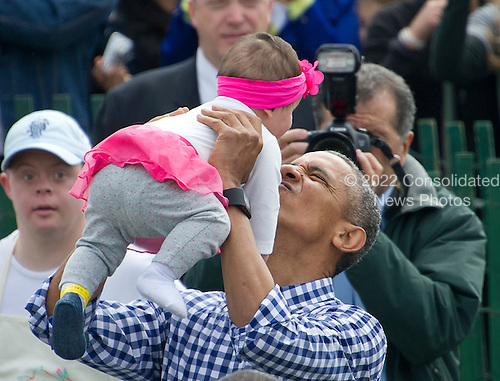 United States President Barack Obama holds up a baby as he and and first lady Michelle Obama host the 2016 White House Easter Egg Roll on the South Lawn of the White House in Washington, DC on Monday, March 28, 2016.<br /> Credit: Ron Sachs / CNP