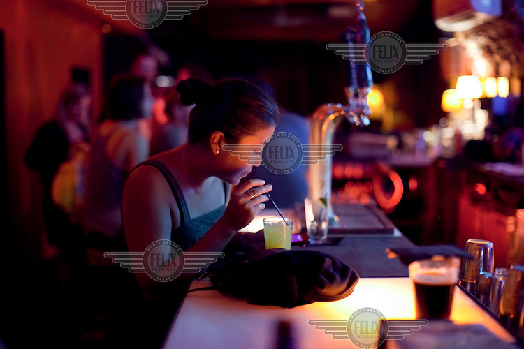 A woman drinks alone at a bar in Alphabet City, New York.