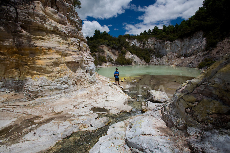 A tourist walks through the geothermal site, Wai-O-Tapu Thermal Wonderland, near Rotorua on the North Island of New Zealand.