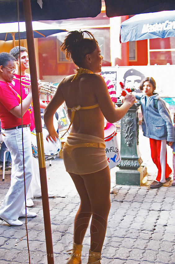 A street performer dancing Latin dances dressed in a very small yellow thong tanga bikini, a young girl watching in amazement and a trumpeter playing, in the restaurant El Palenque, the sword fish swordfish, in the Mercado del Puerto, the market in the port harbour harbor where many people go and eat and shop on weekends Montevideo, Uruguay, South America