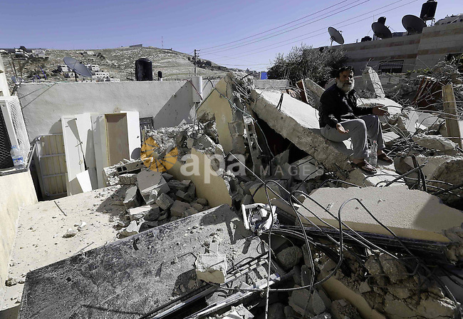 A Palestinian man sits on the rubble of his house after it was demolished by Israeli municipality diggers that the authorities believe without municipal permission in Jabal al-Mukabbir neighborhood south Jerusalem, on Feb. 05, 2014. Israeli authorities ordered the demolition of three Palestinian houses built without permits in the Arab quarters of Sur Bahir village, Beit Hanina and Jabal al-Mukabbir neighborhood housing a total of 25 people, according to residents. Photo by Saeed Qaq