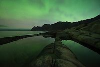 Northern lights reflect in tidal pools at Tungeneset viewpoint, Senja, Norway