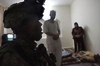 A US soldier from C Company, 1st battalion, 506th, 101st airborne division gurads an iraqi couple in their home while his unit is providing sniper coverage and observation during a night raid with the purpose of arresting two suspected major figures of the Sunni insurgency in their sector in Eastern Ramadi, Al Anbar province, Iraq on WED Jan 11 2006. the mission was divided into two sections. SECTION ONE  with the prurpose of blocking the suspected insurgents from escaping and providing sniper fire for the area and SECTION 2 raiding the house were the two were suppose to be hiding. the two suspected insurgents were nt to9o be found.