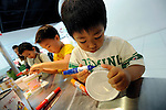 Children enjoy designing their own original cup noodle cups at the My Cup Noodle Factory inside the Momofuku Ando Instant Ramen Museum in Osaka, Japan on 20 October 2008. .Photographer: Robert Gilhooly