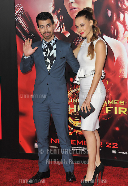 Joe Jonas &amp; Blanda Eggenschwiler at the US premiere of &quot;The Hunger Games: Catching Fire&quot; at the Nokia Theatre LA Live.<br /> November 18, 2013  Los Angeles, CA<br /> Picture: Paul Smith / Featureflash