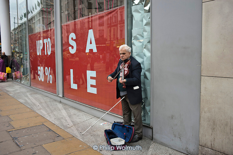 A blind busker plays the violin during post-Christmas sales in Oxford Street, London.