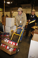 "Friday, February 15, 2013.   Volunteer Sean Porter wheels cans of hot chocholate through the isles as Pat Hensmanns  keeps track of what checkpoints they go to during the ""people food"" drop day at Airland Transport in Anchorage."