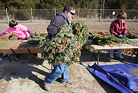 NWA Democrat-Gazette/DAVID GOTTSCHALK Rick McKee (center) distributes wreaths Friday, March 9, 2018, during the the 6th annual Wreath Recycling Project for Bo's Blessings at the Arkansas National Guard Armory in Fayetteville. Bo's Blessings LUTHAB, Inc., collects and then removes the wiring and bows on more than 8,500 wreaths that were distributed on the grave sites at the Fayetteville National Cemetery. The greenery will be used mulch and wire will be collected by the city of Fayetteville Recycling and Trash Collections.