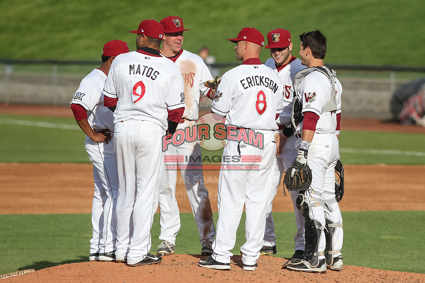 Wisconsin Timber Rattlers shrtstop Gregory Munoz (7), third baseman Sthervin Matos (9), second baseman Tucker Neuhaus (10), first baseman Alan Sharkey (18), catcher Carlos Leal (11) and manager Matt Erickson (8) gather on the mound during a pitching change during a Midwest League game against the Beloit Snappers on May 30th, 2015 at Fox Cities Stadium in Appleton, Wisconsin. Wisconsin defeated Beloit 5-3 in the completion of a game originally started on May 29th before being suspended by rain with the score tied 3-3 in the sixth inning. (Brad Krause/Four Seam Images)