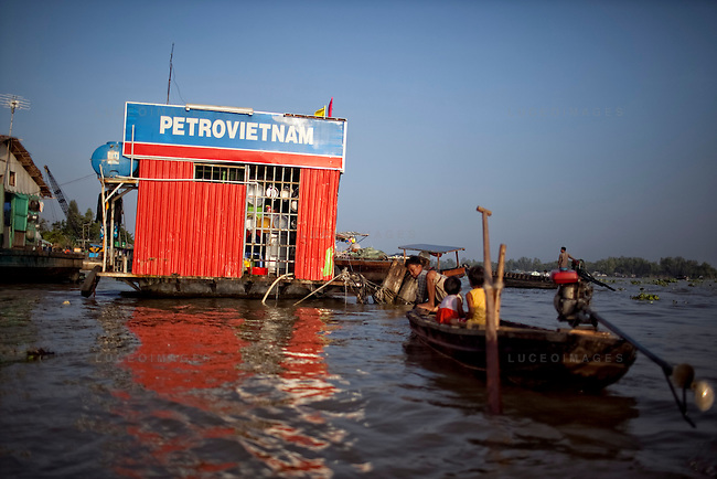 "Boats dock at a gas station on the Hau Giang River, a tributary of the Mekong River, in Long Xuyen, the capital of An Giang Province, Vietnam. When the Mekong River reaches Vietnam it splits into two smaller riveres. The ""Tien Giang"", which means ""upper river"" and the ""Hau Giang"", which means ""lower river"". Photo taken on Monday, December 8, 2009. Kevin German / Luceo Images"