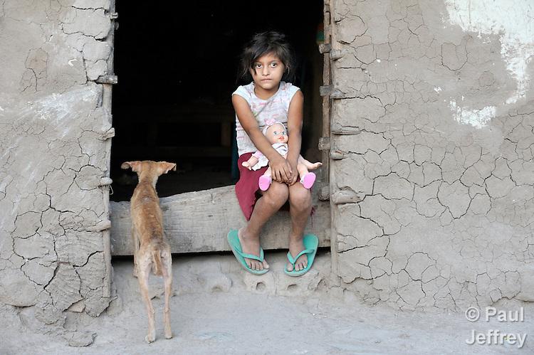 A Honduran girl in the doorway of her adobe house.