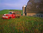 Whitman County, WA:  Vintage red Ford flatbed truck parked in front of a weathered barn and silo in summer