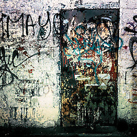 A rusty door, covered by torn down posters and sprayed writings, seen in the center of San Salvador, El Salvador, 18 December 2013.