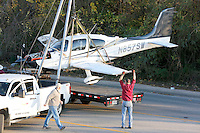 NWA Democrat-Gazette/DAVID GOTTSCHALK  Personnel with Dawson Aircraft Inc. prepare, lift and transport the small plane that crashed Tuesday, November 3, 2015, on Martin Luther King Boulevard in Fayetteville. Bill Simon, 56, Cliff Slincard, 59, and Maurice Willis, 47, were on the plane that deployed an emergency parachute attached to the plane after an attempt at making an emergency landing at Drake Field in Fayetteville. The plane took off from Bentonville airport. All three men were transported to area hospitals with non life threatening injuries.
