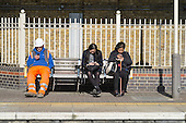 Construction worker and two women use mobiles on a station platform, London.