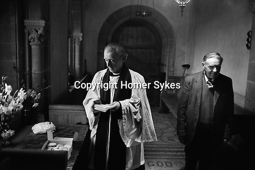 Pax Cake distribution, St Catherine's church, Hoarwithy, Hereford and Worcester. England 1974 Palm Sunday. The Revd. Idris Michael Evans, the Vicar of Hentland with Hoarwithy and Sidesman  Mr Stan Jones. The image on the Pax cake is the 'Agnus Dei', the Lamb of God.<br />
