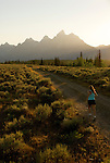 A young woman runs down a dirt road at sunset in Grand Teton National Park, Jackson Hole, Wyoming.