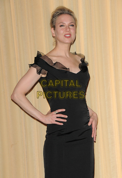 RENEE ZELLWEGER .attends The International Women's Media Foundation's Courage in Journalism Awards held at The Beverly Hills Hotel in Beverly Hills, California, USA, October 16th 2008                                                                     .half length black ruffle trim dress hand on hip .CAP/DVS.©Debbie VanStory/Capital Pictures