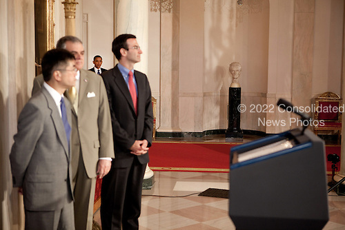 Washington, DC - June 1, 2009 -- United States President Barack Obama (background) walks to the podium in the Grand Foyer of the White House to make an announcement about General Motors and the auto industry June 1, 2009. In the foreground are members of his Cabinet, (left to right) Gary Locke, Secretary of Commerce, Ray LaHood, Secretary of Transportation, and Peter Orszag, Director of the Office of Management and Budget. .Mandatory Credit: Chuck Kennedy - White House via CNP