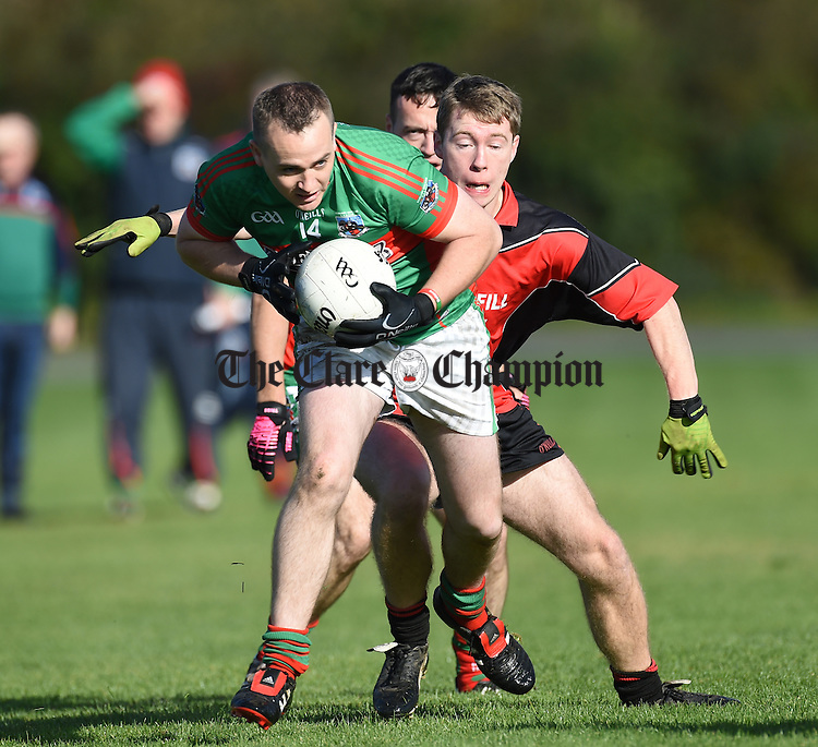 Stephen Downes of Kilmurry Ibrickane  in action against Peter Reidy of Meelick during their Junior A  county final at Gurteen. Photograph by John Kelly.