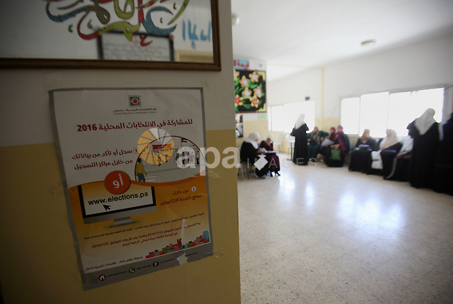 Palestinians look for their names on the registered voters' list at Voter registration centers in the West Bank city of Nablus on July 24, 2016. The Palestinian Central Elections Commission (CEO) announced Saturday that voter registration centers would be open from Saturday until Wednesday in all local and municipal councils across the occupied West Bank and Gaza Strip in preparations for the upcoming local elections in October. Photo by Nedal Eshtayah