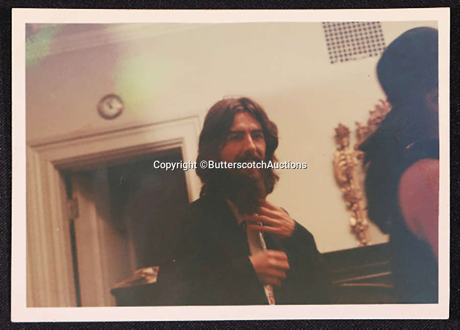 BNPS.co.uk (01202 558833)<br /> Pic: ButterscotchAuctions/BNPS<br /> <br /> A smiling George Harrison.<br /> <br /> Candid unseen photos which show John Lennon and George Harrison relaxing away from the public gaze a year after The Beatles split have been unearthed.<br /> <br /> The five intimate snaps were taken by a music executive who worked with the pair in New York on the Let It Be album, The Beatles' final album, and would even fill in for producer Phil Spector during his collaborations with Lennon.<br /> <br /> He built up a friendship with Harrison which endured after the fab four went their separate ways and photographed both former Beatles' at a New York apartment in the lead up to Harrison's Concert for Bangladesh in August 1971.<br /> <br /> However, things are rumoured to have turned sour between Harrison and Lennon shortly after this meeting as Lennon allegedly reneged on his agreement to perform at the fundraising concert without his wife Yoko Ono.