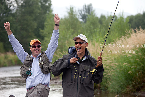 Belgrade, MT - August 14, 2009 -- Local fishing guide Dan Vermillion reacts as United States President Barack Obama hooks a trout on the East Gallatin River near Belgrade, Montana, August 14, 2009.  The President hooked about 6 fish, but did not land any during his first fly fishing outing.  .Mandatory Credit: Pete Souza - White House via CNP