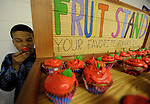 """Andrew Curtis, 10, of Vernon, gets to sneak a cupcake, with permission from his sister Nicole, from her display, during """"Cupcake Extravaganza"""", Thursday evening, April 25, 2013, at Rockville High School. The cupcakes were made by students with staff and sold to raise money for the Hockanum Valley Community Council Food Pantry. Rockville High School culinary teacher Lori Gilmore said before it started that she hoped the first time event for HVCC would raise $2,500. HVCC CEO David Engelson said the food shelves are nearly bare and the funds are desperately needed. Engelson said HVCC will be holding a major fund raiser, a fashion show, Wednesday, May 8, at Maneeley's in South Windsor and is asking for the public to buy tickets to the event or donate food or money to the HVCC located on Naek Road in Vernon. (Jim Michaud /Journal Inquirer)."""