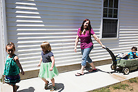 Lora Reyes is a licensed family childcare educator in Westfield, Mass., where she operates the daycare Lora's Little Ones out of her home on Thurs., June 2, 2016. Here she leads the children outdoors for playtime. Today she was in charge of 7 children, aged 14 months to 5 years old, handling meals, playtime, and educational activities throughout the day, starting about 7am and going until 4:30pm. She uses the Mother Goose Time curriculum throughout the day. Reyes is currently pursuing an undergraduate degree in Psychology at Holyoke Community College. She started 2 years ago after earning a Child Development Associate certification.