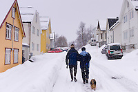 Street scene of couple walking their dog in Tromsoya, Tromso,  Arctic Circle in Northern Norway