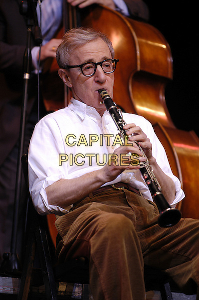 """WOODY ALLEN.In concert with the New York Jazz Ensemble. A benefit evening for """"Ricerca e Progresso Foundation""""..Sistina Theatre, Rome, Italy.half length, sitting, playing musical instrument, clarinet, gesture, glasses.www.capitalpictures.com.sales@capitalpictures.com.© Capital Pictures."""