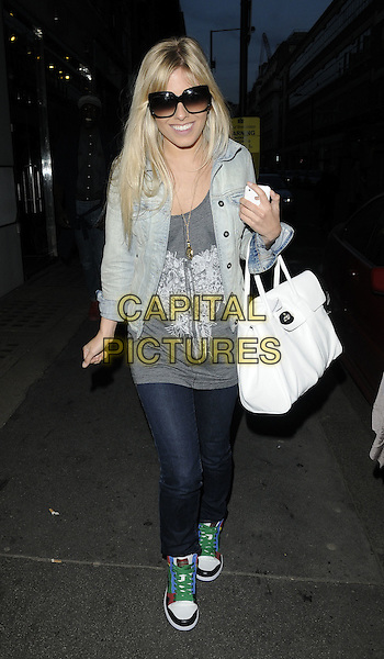 MOLLIE KING (THE SATURDAYS).At the Johnnie B clothing label Launch Party, Oui Rooms, London, England, UK, .April 22nd 2010..full length denim jacket sunglasses grey gray top white Mulberry Bayswater tote bag jeans top green laces trainers smiling walking double denim necklace heart motif print  .CAP/CAN.©Can Nguyen/Capital Pictures.