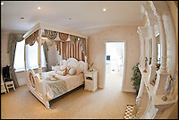 BNPS.co.uk (01202 558833)<br /> Pic: ChrisCowley/EnchantedManor/BNPS<br /> <br /> **Please use full byline**<br /> <br /> A double bedroom.<br /> <br /> Sleeping Beauties and Cinderallas take note - make a wish and this luxury fairytale hotel could be yours for a cool &pound;1.5 million.<br /> <br /> With 11 sumptuous suites - all of which are decked out in fairtytale style with four-poster beds - the Enchanted Manor is the stuff dreams are made of.<br /> <br /> Coupled with idyllic sea views, the unique 5* property near Niton on the Isle of Wight has become a bolthole for couples seeking fairytale romance.<br /> <br /> Once a historic Victorian manor house, owners Ric and Maggie Hilton set about creating their dream come true after saving the grand building from ruin in 2006.<br /> <br /> The property is being on the market for &pound;1.5 million with property guru Sarah Beeny's online estate agents Tepilo.