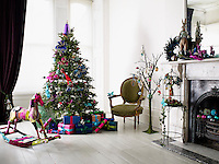 Interior in location house, London. Christmas scene of a large Christmas tree with wrapped, brightly coloured, gift boxes and crackers below. A Squint Antique rocking horse sits beside.