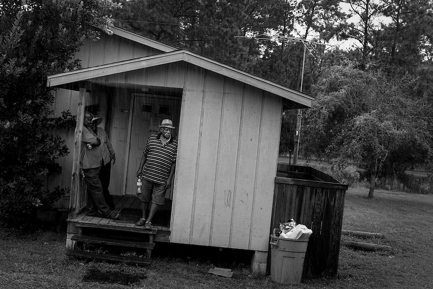 Geechee men in the Hog Hammock community on Sapelo Island seek shelter from the rain on the porch of The Trough, the island's only bar.