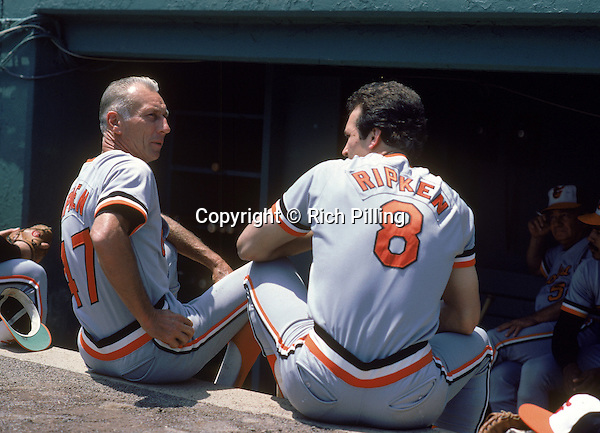 Undated:  (L-R) Cal Ripken Sr. #47 and Cal Ripken Jr. #8 of the Baltimore Orioles talk in the dugout before a season game. Cal Ripken Jr.played for the Baltimore Orioles from 1981-2001. Cal Ripken Sr. was a manager for 1985-1988. (Photo by Rich Pilling)