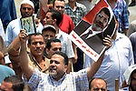 Supporters of Egyptian President Mohamed Mursi shout slogans during a protest to show support to him in front of Cairo University in Cairo July 3, 2013. At least 16 people were killed on Wednesday and 200 wounded when gunmen opened fire on supporters of President Mohamed Mursi who were rallying outside Cairo University, state television quoted a Health Ministry spokesman as saying. Photo by Ahmed Asad