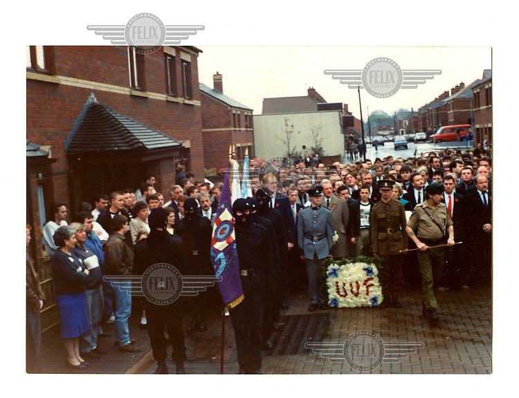 A photographs from Jimmy's family album. A Ulster Volunteer Force (UVF) funeral in Belfast in the late 1980s with full colour brigade. Jimmy's son is one of the men wearing a balaclava. He was later murdered by members of the INLA (Irish Nationalist Liberation Army).